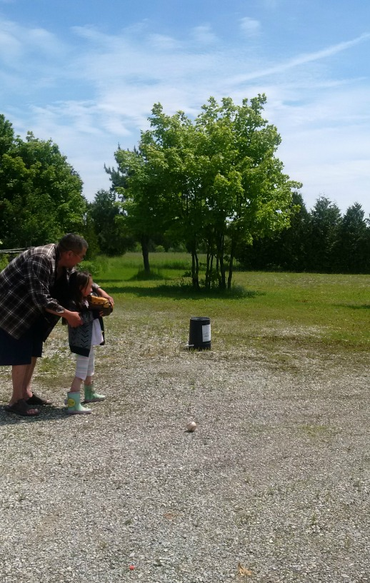 Grampy teaching Little One how to position her feet and elbow when throwing ball.